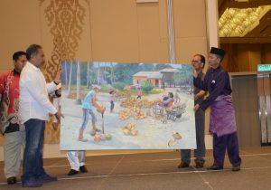 هنرمند مالزیایی نقاشی خود را به رسم یادبود به میمهان مراسم اهدا می کند