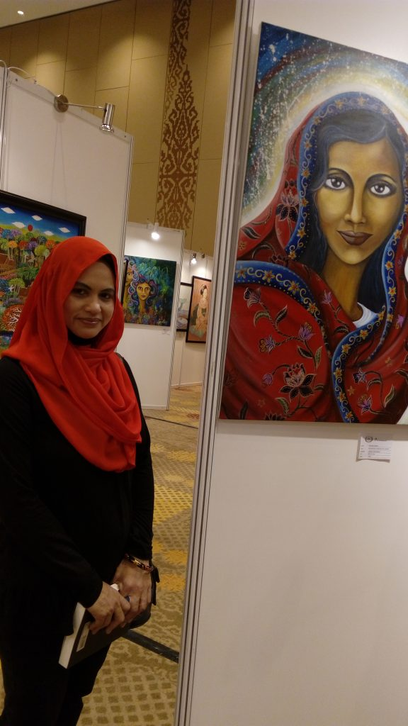 Liza and her paintings, in foreground  and background